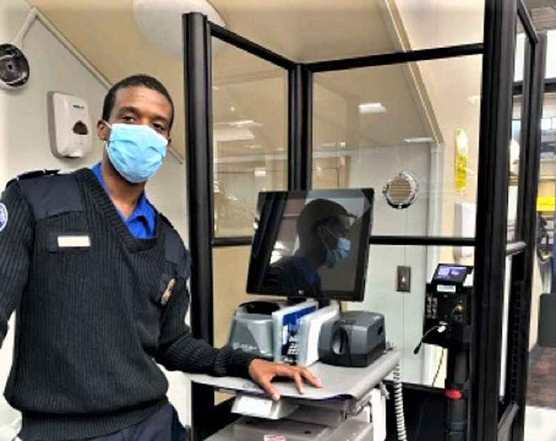 A TSA officer staffs the travel document checking station with a new credential authentication technology unit at HPN.