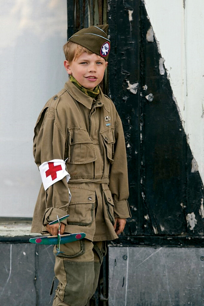 A French boy dressed as a U.S. Paratrooper smiles for a photo during D-Day celebration at Ste. Marie Eglise